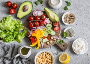 healthy Mediterranean Diet foods on a concrete table olive oil, avocado, tomato nuts